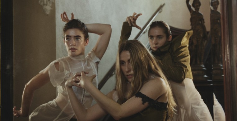 A portrait of three dancers with averted gaze and tension in their fingers.