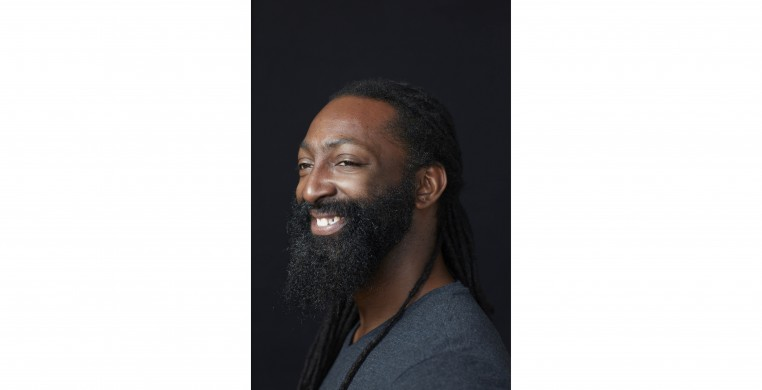 Mr. Hunter: A Native American African-American person with dark chocolate skin from his mother. He has almond shaped eyes with long lashes. He has long black dreadlocks tied in a low braid and a full beard. Antoine is wearing a dark v-neck shirt and smili