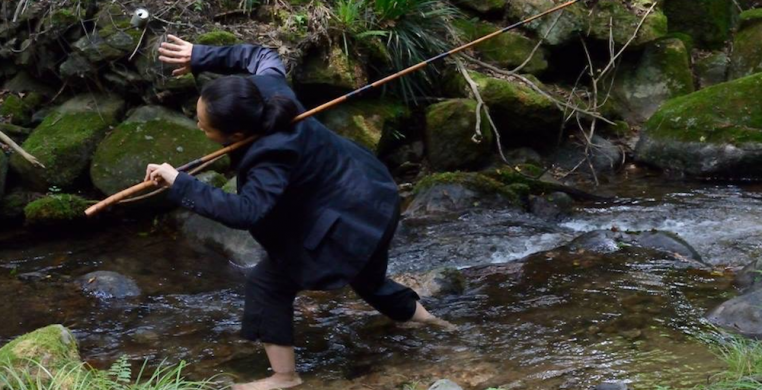 Ayako Kato by Yasunori Hangoh. A person dressed in a black suit jacket and black pants wades barefoot through a stream carrying a wooden fishing pole over one shoulder.