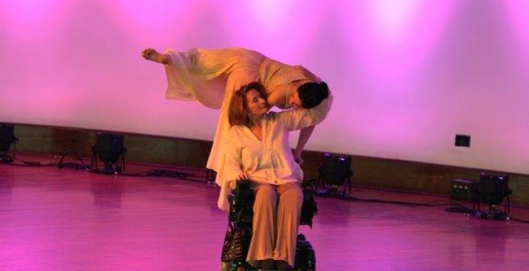 Two women in pastel, the younger climbs on the elder dancers power wheelchair. they look into each others eyes.