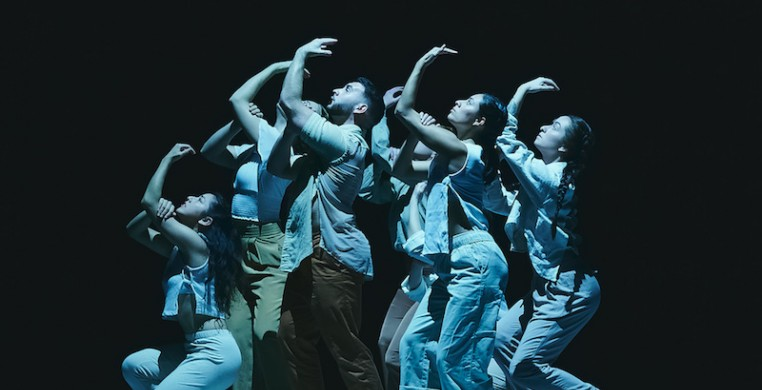 Six dancers are in a group close together in profile looking up, some crouching and some standing. All the dancers have their left arm reaching up, with their right hand clasping their left bicep.